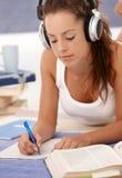 Trabalhos de casa atrativos da escrita da menina que colocam no assoalho imagem de stock