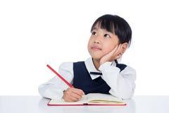 Trabalhos de casa chineses pequenos asiáticos da escrita da menina fotografia de stock