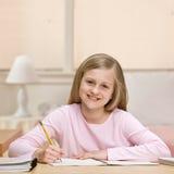 Trabalhos de casa da escrita da rapariga no caderno imagem de stock