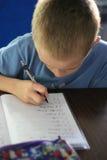 Trabalhos de casa da escrita do menino Imagem de Stock