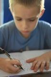 Trabalhos de casa da escrita do menino Imagem de Stock Royalty Free