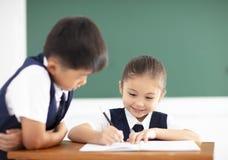 Trabalhos de casa da escrita da menina na sala de aula Imagens de Stock
