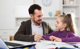 Trabalhos de casa de Helping Daughter With do pai Imagens de Stock Royalty Free