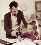 Trabalhos de casa de Helping Daughter With do pai Fotografia de Stock Royalty Free