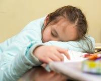 Trabalhos de casa fazendo adormecidos de queda da moça Fotografia de Stock