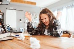 trabalhos de casa de jogo da menina cansado da criança com erros fotos de stock