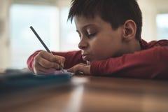 Trabalhos de casa novos da escrita do menino Imagem de Stock