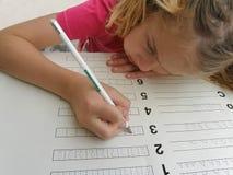 Trabalhos de casa writening da matemática da menina bonita Foto de Stock