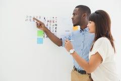 Trabalhos de equipa concentrados que apontam a imagem e a informação Fotos de Stock Royalty Free
