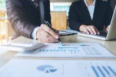 Trabalhos de equipa da análise dos colegas do negócio dois com dados financeiros imagens de stock