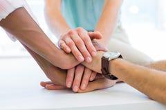 Trabalhos de equipa da mostra dos colegas trazendo as mãos junto Fotografia de Stock Royalty Free
