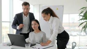 Trabalhos de equipa dos empresários no portátil na sala de reuniões, conceituando trabalhadores de escritório no computador no ce