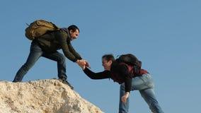 Trabalhos de equipa dos executivos Os turistas d?o a m?o entre si, escalando para cobrir do monte a equipe dos viajantes masculin filme