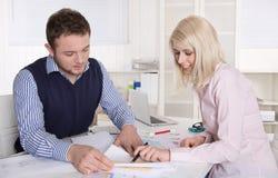 Trabalhos de equipa entre dois colegas do trabalho na mesa no escritório. Fotos de Stock