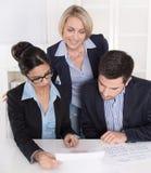 Trabalhos de equipa entre três executivos na mesa no escritório. Fotos de Stock Royalty Free