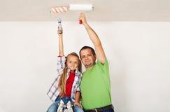 Trabalhos de equipa - pai orgulhoso e filha que pintam a sala Imagem de Stock
