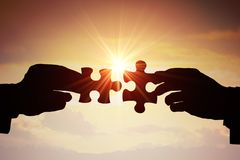 Trabalhos de equipa, parceria e conceito da cooperação Silhuetas de duas mãos que juntam-se a duas partes de enigma junto