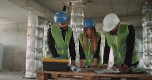 Trabalhos de equipa de três coordenadores que analisam o plano do esquema da construção filme