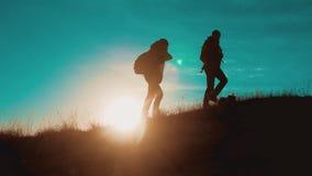 Trabalhos de equipe que superam o sucesso da vitória das dificuldades dois homens dos caminhantes da silhueta dos turistas com as vídeos de arquivo