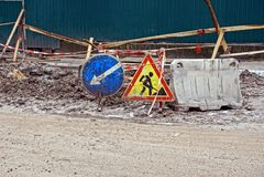 Trabalhos de estrada na estrada com sinais do poço e de estrada Imagem de Stock