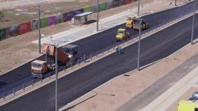 Trabalhos de estrada - os trabalhadores colocam o asfalto na cidade Vista geral vídeos de arquivo