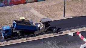 Trabalhos de estrada - os trabalhadores colocam o asfalto na cidade Vista geral video estoque