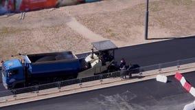 Trabalhos de estrada - os trabalhadores colocam o asfalto na cidade vista geral, vídeo acelerado vídeos de arquivo