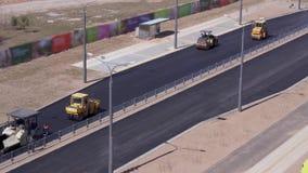 Trabalhos de estrada - os trabalhadores colocam o asfalto na cidade vista geral, v?deo acelerado vídeos de arquivo