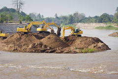 Trabalhos de grupo da máquina da máquina escavadora no rio Fotos de Stock