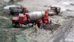 Trabalhos diminutos dos trabalhadores com o caminhão do misturador de cimento imagens de stock