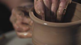 Trabalhos do homem com roda e argila de oleiro A cer?mica do handwork e a argila acautelam-se video estoque