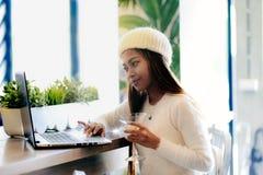 Trabalhos em rede bonitos da menina em um café com portátil Fotos de Stock