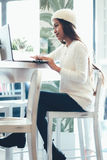 Trabalhos em rede bonitos da menina em um café com portátil Fotos de Stock Royalty Free