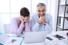 Trabalhos em rede dos trabalhadores de escritório com um portátil Foto de Stock