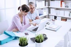 Trabalhos em rede dos trabalhadores de escritório com um portátil Fotos de Stock