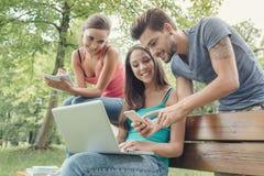 Trabalhos em rede sociais dos adolescentes felizes no parque Imagem de Stock