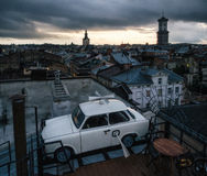 Trabant car parked on the roof a historic building House of Legends in the dusk. Lviv, Ukraine Royalty Free Stock Images