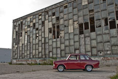 Trabant - socialistic car. Red socialistic Trabant car in front of old factory shop Royalty Free Stock Photos