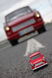 Trabant toy. Red Trabant toy against real red Trabant car Stock Photo