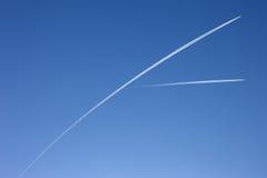 Tracce dell'aeroplano attraverso un cielo blu puro Immagini Stock Libere da Diritti