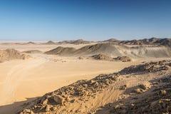 Tracce dell'automobile sulla sabbia nel deserto contro il contesto Immagini Stock