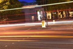 Tracce della luce dei bus e delle automobili alla notte su una strada urbana a Londra, Regno Unito Immagini Stock