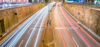 Tracce della luce dell'automobile dell'entrata del tunnel alla notte fotografia stock