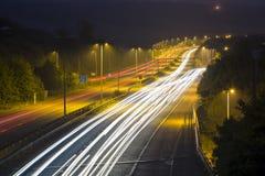 Tracce della luce dell'autostrada alla notte Immagine Stock