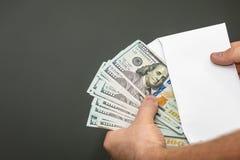 Tracción del dinero fuera de un sobre imagen de archivo