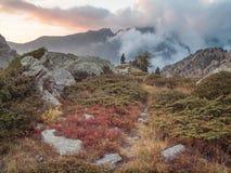Traccia attraverso il paesaggio della montagna con la nuvola bassa al tramonto Immagini Stock