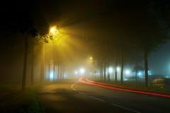 Traccia dell'automobile su una strada vuota di notte in una nebbia Immagine Stock