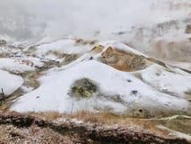 Traccia di camminata di legno bagnata del sentiero per pedoni della valle dell'inferno di Jigokudani con la foschia enorme dello  fotografia stock libera da diritti