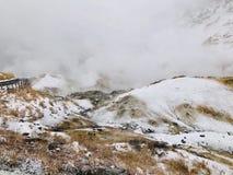 Traccia di camminata di legno bagnata del sentiero per pedoni della valle dell'inferno di Jigokudani con la foschia enorme dello  fotografie stock