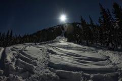 Traccia di freeride dello sci alla notte nella luce della luna Immagini Stock
